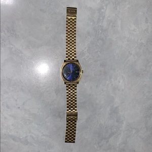Gold Nixon watch with deep blue face